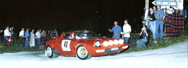 A Lancia Stratos rounds a dusty corner during 1970s nighttime competition