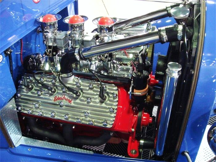 An old-school Ford flathead V8 with triple Strombergs provides the power