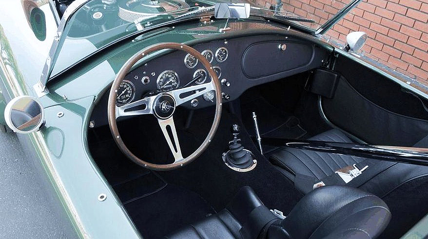 The restored interior features an original AC steering wheel