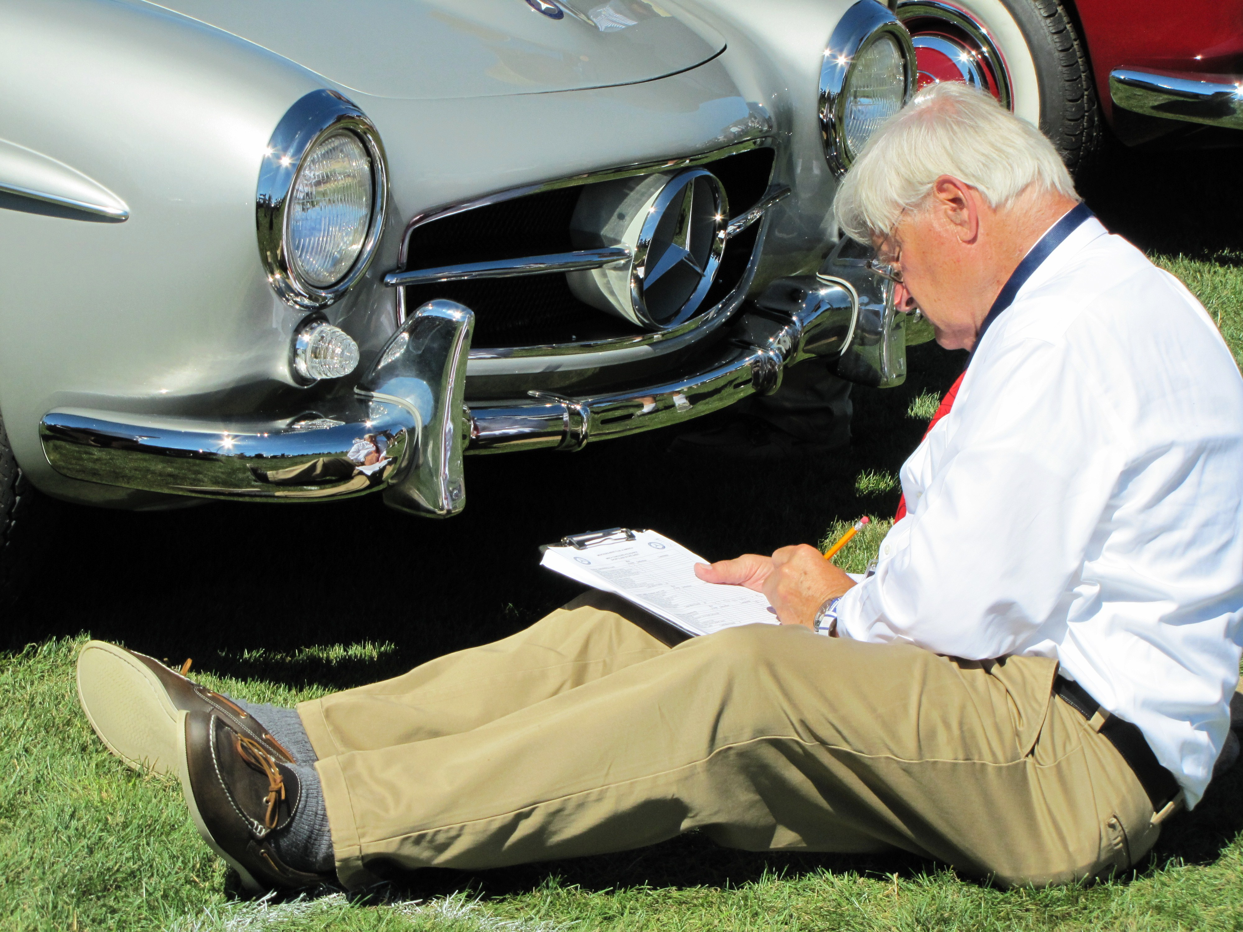 A concours Judge inspects a Mercedes-Benz 190SL at Legends of the Autobahn 2015 event | Bob Golfen photo