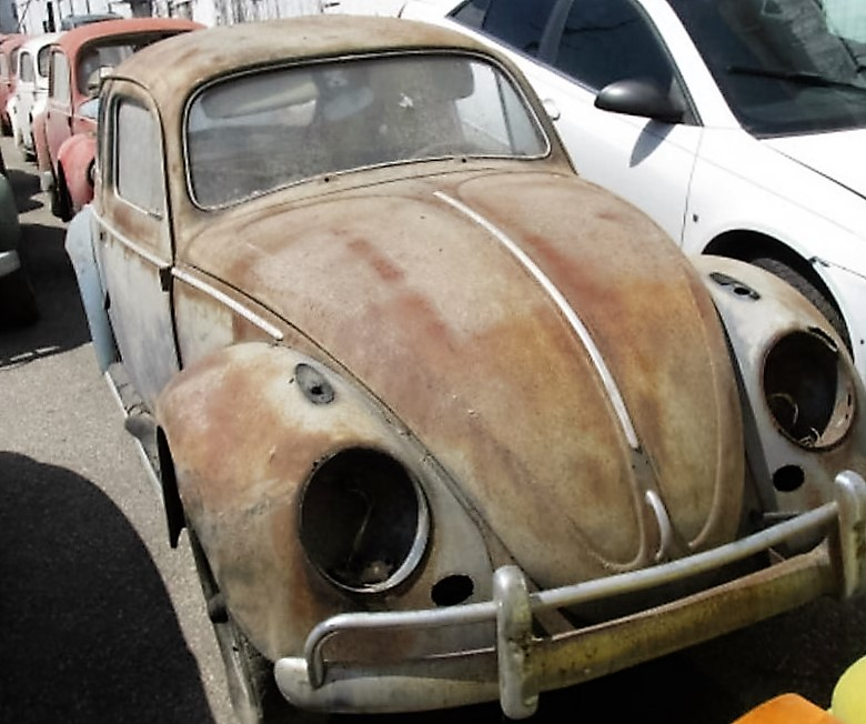 A rusty VW beetle after being removed from the building | Hoge