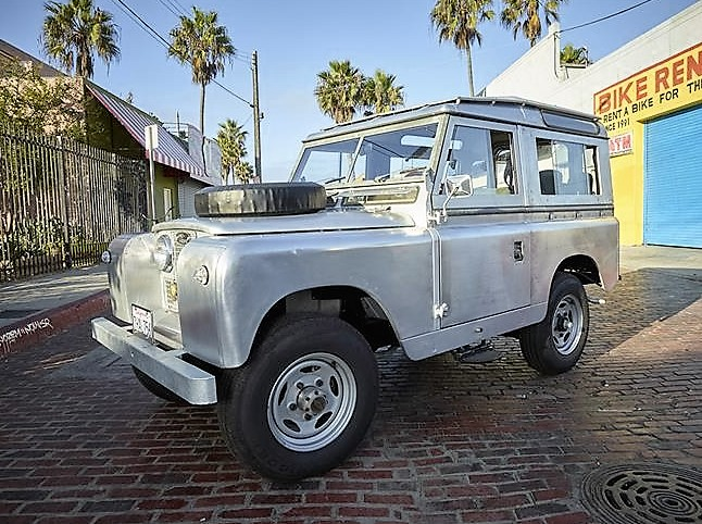 The 1965 Land Rover gleams in its unpainted aluminum finish