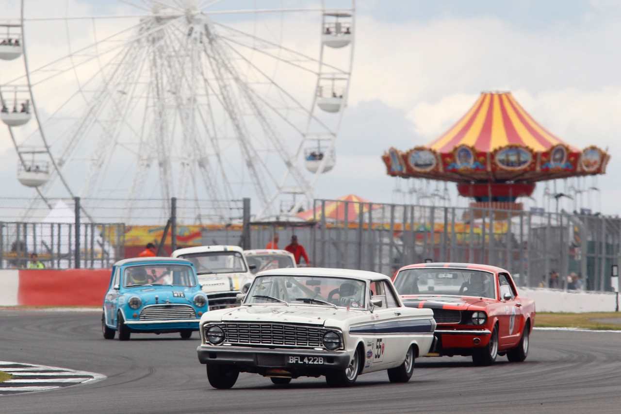 Vintage sports sedans race past the Ferris wheel and Merry-Go-Round at Silverstone Classic | Silverstone Classic photos