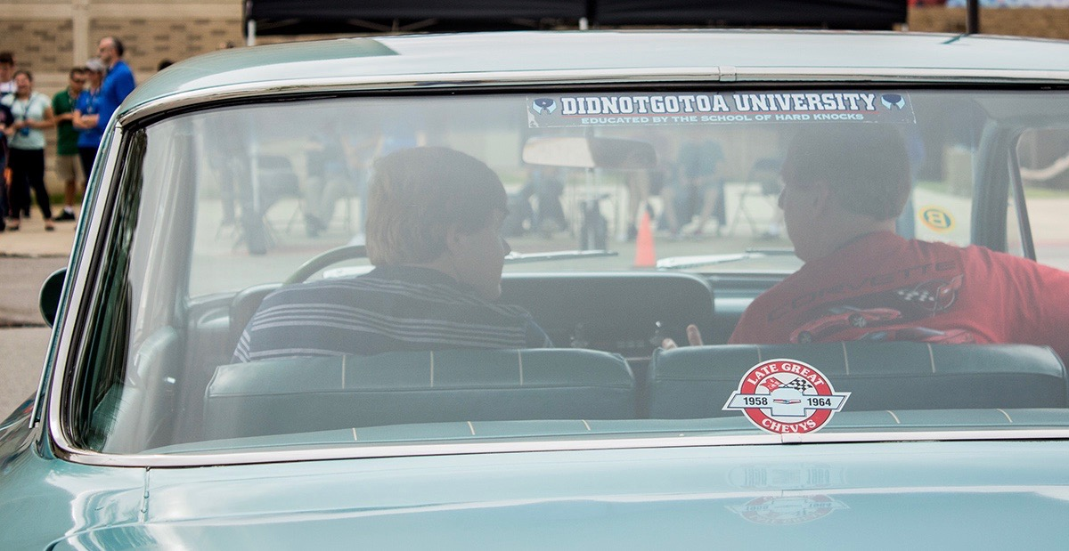 Peeking over their shoulders as student learns from the car owner