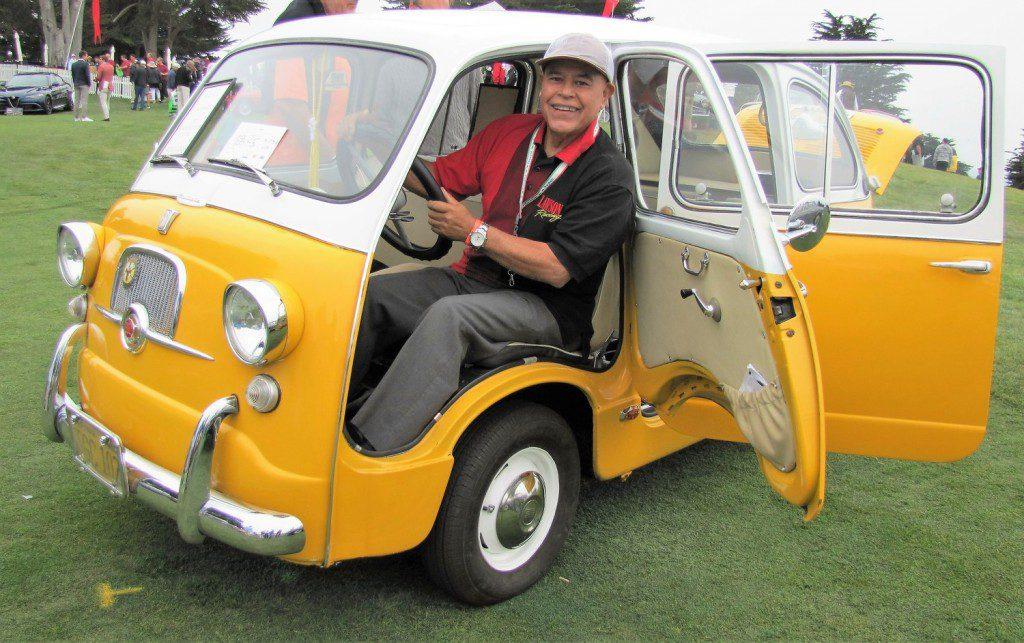 Ruben Ruiz grins from his 1958 Fiat Multipla at Concorso Italiano