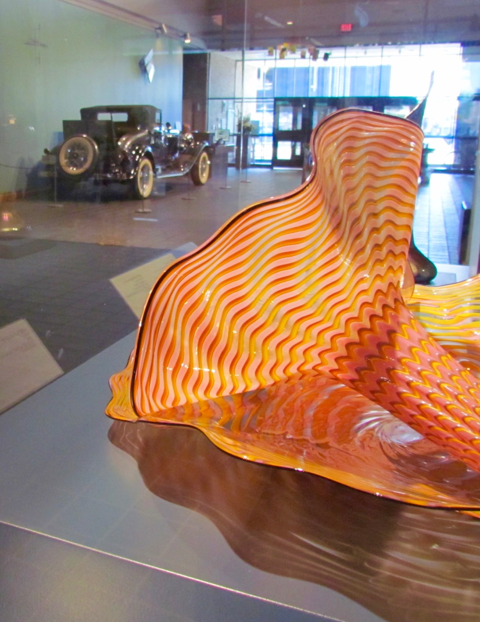 Chihuly glass sculpture in museum lobby with 1934 Auburn 1250