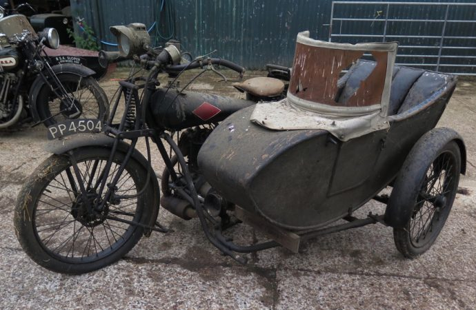 Four vintage motorcycles with sidecars going from barn to auction
