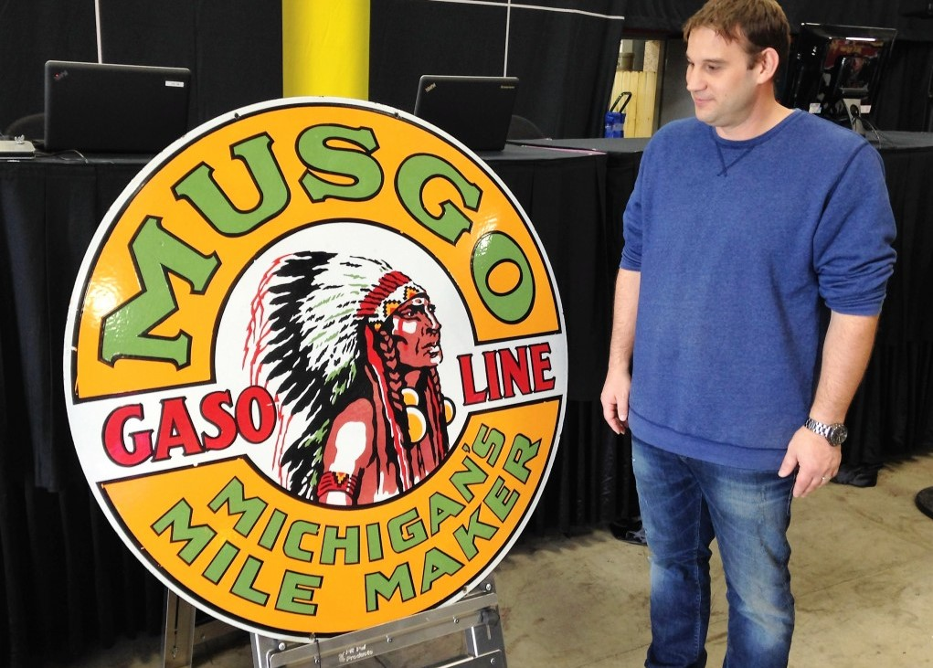 Dan Mecum, Road Art division chief, with the record-setting Musgo sign | Mecum Auctions photos