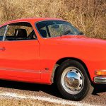 The Karmann Ghia coupe wears a fresh orange paint job