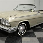 The gold Impala is nicely outfitted with narrow whitewalls and spinner hubcaps