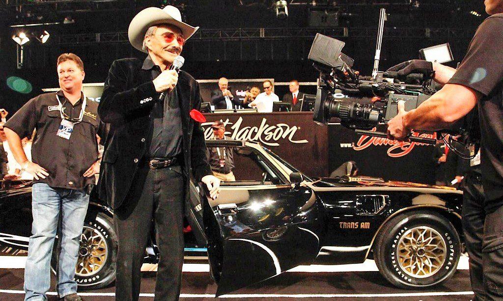 Veteran actor Burt Reynolds with a 1977 Pontiac Firebird Trans Am from 'Smoky and the Bandits' | Barrett-Jackson