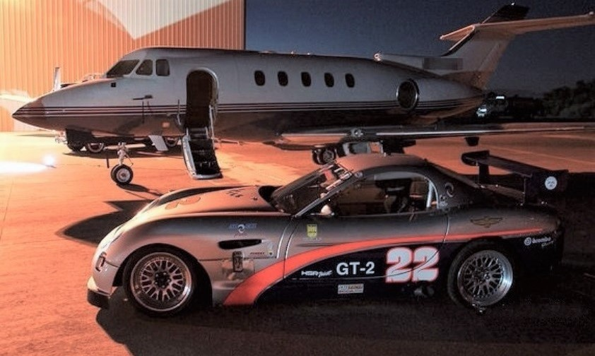 A Panoz GT-2 and a jet plane parked on the tarmac | Jet Center events