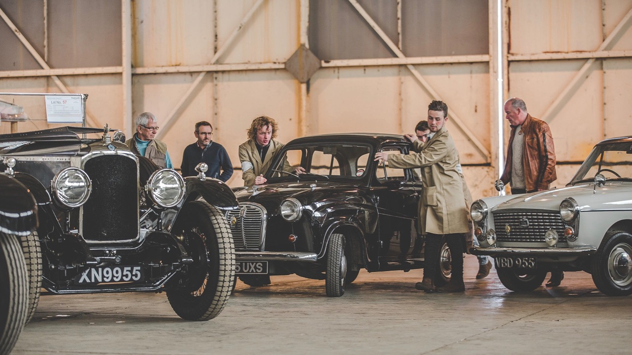 Cars are maneuvered into place for the auction | Bicester Heritage photos