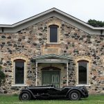 An 1932 Alfa Romeo 8C 2300 posing in front of a rural building in Elkhart Lake
