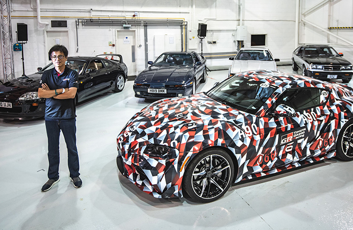 Tetsuya Tada, the chief engineer of the new A90 Toyota Supra, poses with his creation and examples from the past four Supra generations. | Toyota GB photo