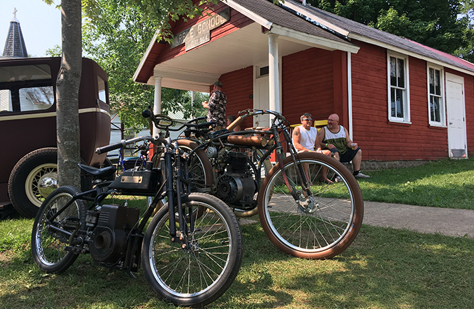 Vintage motorcycles sit in the shade of an old schoolhouse at the annual Symco Weekender. | William Hall photo