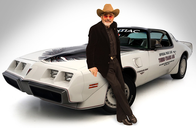 Actor Burt Reynolds poses with one of his Pontiac Trans Ams. The Smokey and the Bandit star passed away Thursday at 82. | Barrett-Jackson photo