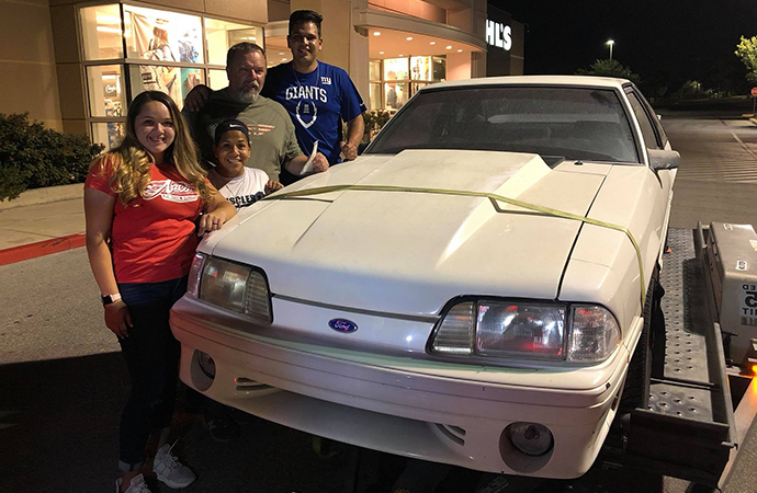 The Ryan family poses with their dad's 1993 Ford Mustang he sold 17 years ago to pay their mother's medical bills. Now cancer-free, she helped her children surprise their father with the gift. | Facebook photo