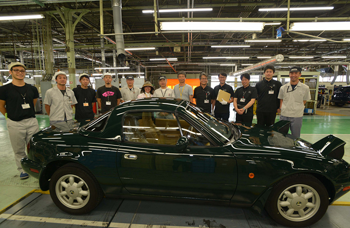 Keiji Nishimoto and his wife, Norimi, pose with officials and workers who restored their 1992 Eunos Roadster -- sold as a Mazda MX-5 Miata in the U.S. -- under a program launched last year. | Mazda photo