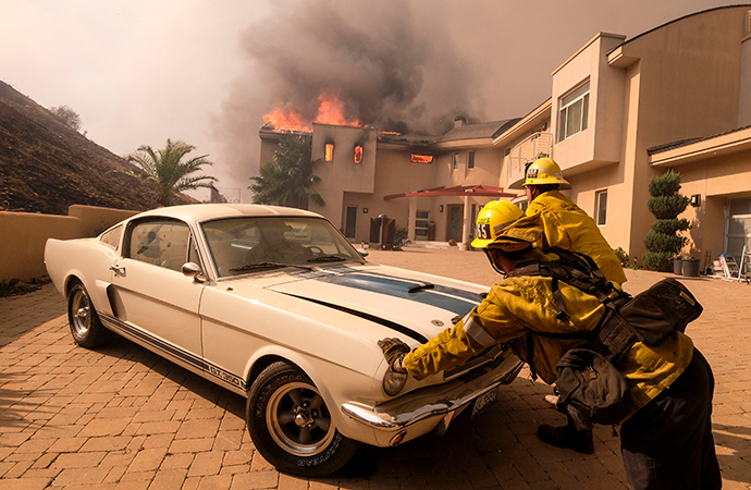 Firefighters push a vehicle from a garage as the Woolsey fire burning a home near Malibu Lake in Malibu, Calif., Friday, Nov. 9, 2018. | AP Photo/Ringo H.W. Chiu