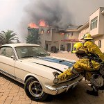 -5c265d9856cea–5c265d9856cedFirefighters push a vehicle from a garage as the Woolsey fire burning a home near Malibu Lake in Malibu, Calif., Friday, Nov. 9, 2018. AP Photo Ringo H.W. Chiu.jpg