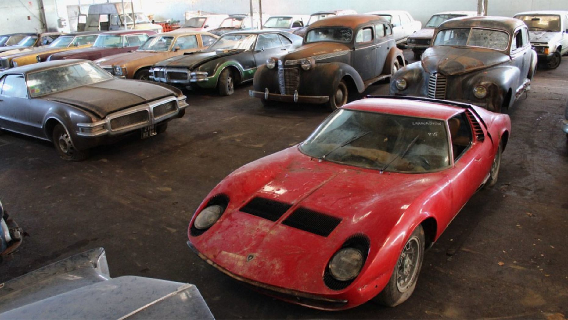 After French collector's death, more than 80 cars were discovered in buildings and outdoors, including a Lamborghini Miura. The big barn find will be offered at auction. | Interencheres photo